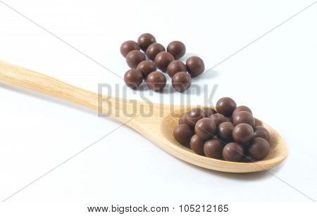 Wooden Spoon Full Of Herbal Cough Lozenges On White Background