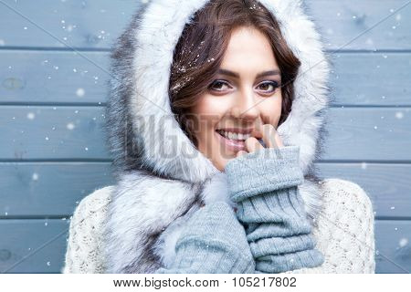 Beautiful young smiling brunette woman wearing knitted sweater and fur hood, covered with snow flakes. Snowing winter beauty concept.