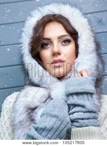 Beautiful young pensive brunette woman wearing knitted sweater and fur hood, covered with snow flakes. Snowing winter beauty concept.