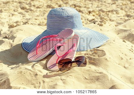 Flip flops, sunglasses and hat on beach sand closeup