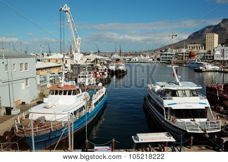 CAPE TOWN, SOUTH AFRICA -FEBRUARY 20, 2012: Victoria and Alfred Waterfront, harbor with boats, shops and restaurants popular with tourists.