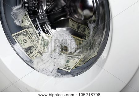Laundering of money in washing machine, close up