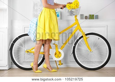 Girl with yellow retro bicycle in spacious bright room