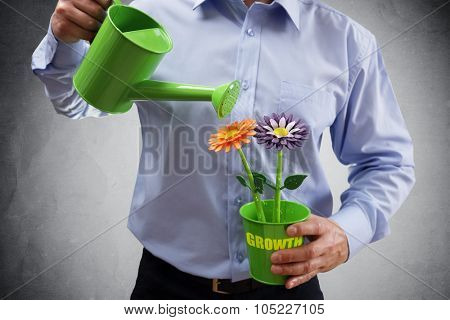 Investment and growth businessman with watering can investing in business and making money concept