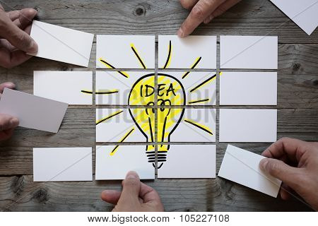 Business team brainstorming and finding a solution or good idea with light bulb drawing on business card paper