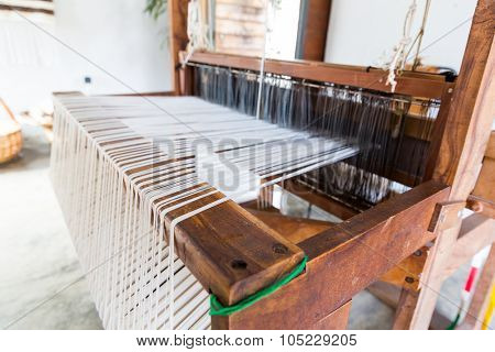 Old shuttleless loom with black and white wools working in the room
