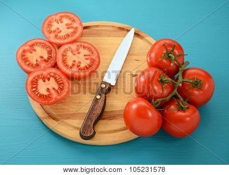 Tomatoes, Whole And Sliced With Knife On Wooden Board