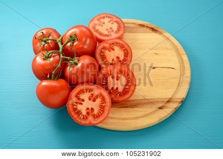 Vine Tomatoes Whole And Halved On A Circular Board