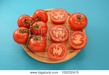 Tomatoes - On The Vine, Halved And Whole On A Wooden Board