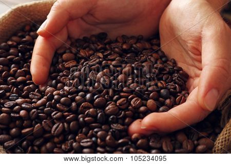 Hands in sac with roasted coffee beans
