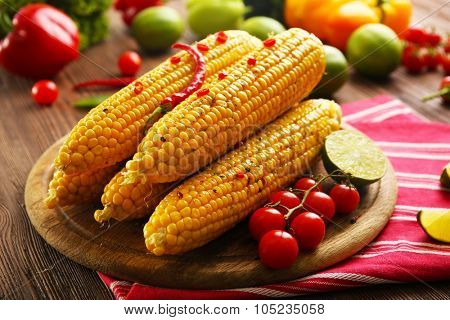 Grilled corn served with vegetables on rustic round plate