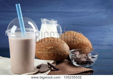 Plastic cup of milkshake on color wooden background