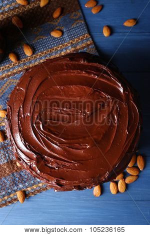 appetizing chocolate cake among almonds on blue background