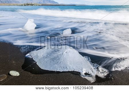 Beautiful beach in the South of Iceland with a black lava sand is full of icebergs washed by the sea