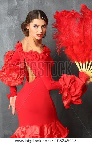 Beautiful dancer in a red dress with a red plumage fan in hands stands half-turned