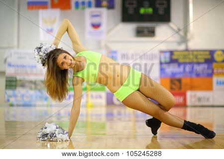 Portrait of girl cheerleader performs a rack on her side, leaning right hand on the floor with shiny pompons in the gym
