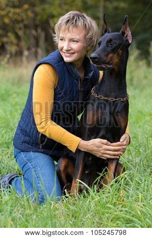 Smiling woman is sitting on the lap hugging a dobermann in park.
