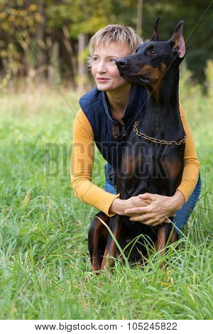 Woman is sitting on the grass and hugging a dog, focus on a dog.