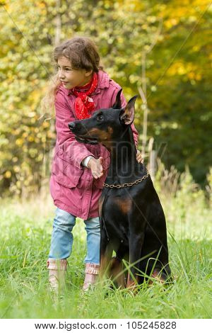 Little curly girl and dobermann are looking to the right in park, focus on a dog.