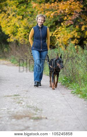 Smiling woman is walking with dobermann in a park.