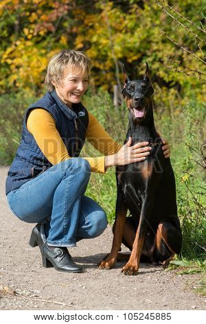 Smiling woman at beige polo-neck is hugging dobermann in a park.