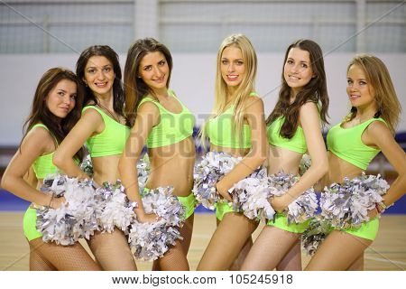 Portrait of six beautiful cheerleaders with silvery pompons in the gym