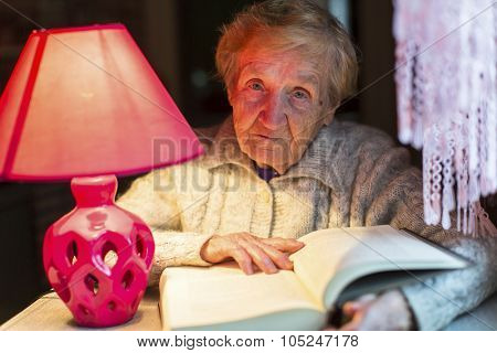 Elderly woman reading a book sitting at a table with a lamp.