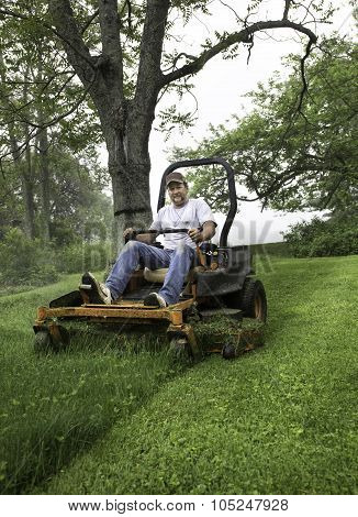 Man mower grass on riding lawnmower