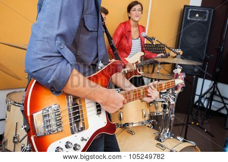 Midsection of man playing guitar with female singer in recording studio