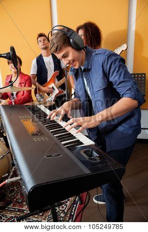 Smiling young man playing piano while band performing in recording studio