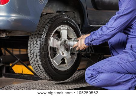 Midsection of male mechanic screwing car tire with pneumatic wrench at garage