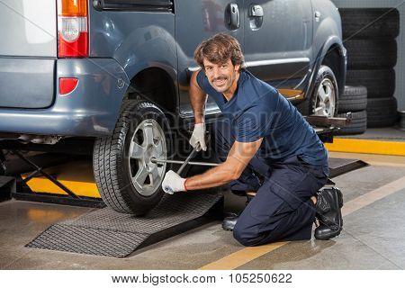 Portrait confident male mechanic using rim wrench to fix car tire at auto repair shop