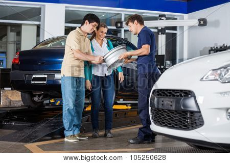 Male technician and couple examining metallic alloy at garage
