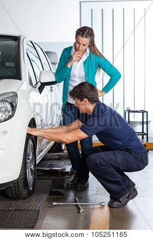 Female customer looking at mechanic changing car tire at garage