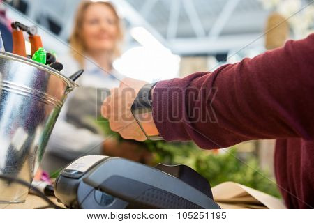 Cropped image of female customer paying through smart watch at flower shop