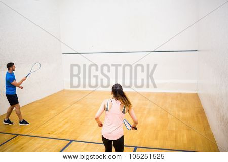 Competitive couple playing squash together in the squash court
