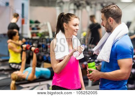 Fit couple chatting in weights room at the gym