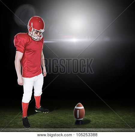 Unsmiling american football player looking down against lens flare