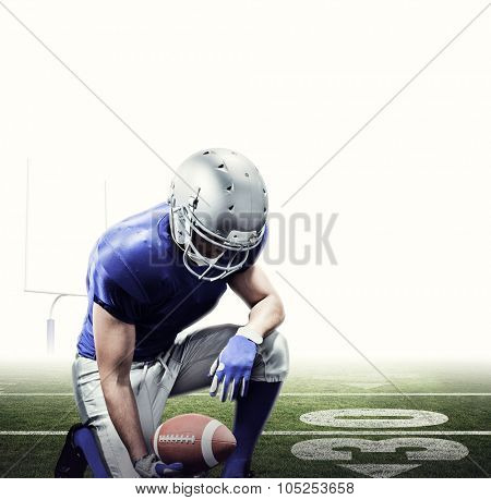 American football player kneeling while holding ball against american football posts