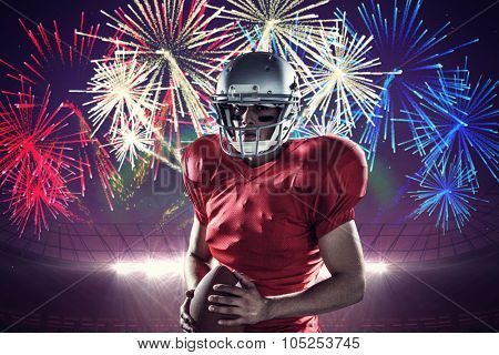 Portrait of determined sportsman with American football against fireworks exploding over football stadium