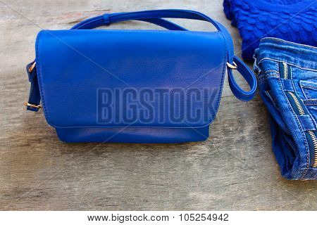 Women's clothing and accessories: blue sweater, jeans, handbag on wooden background.