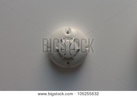 Fire Alarm Sensor On White Wall Background, Top View