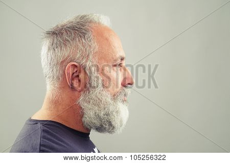 sideview of senior bearded man over light grey background with empty copyspace