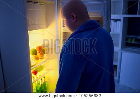 overweight guy at night open refrigerator looking for food
