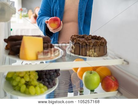 Fat man on diet take healthy apple from fridge instead of hard food
