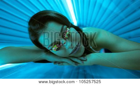 Woman in bed solarium with protect glasses