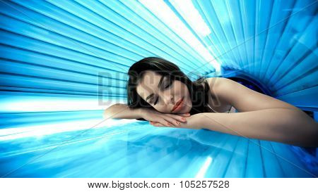 Young woman  having tanning skin treatment in solarium