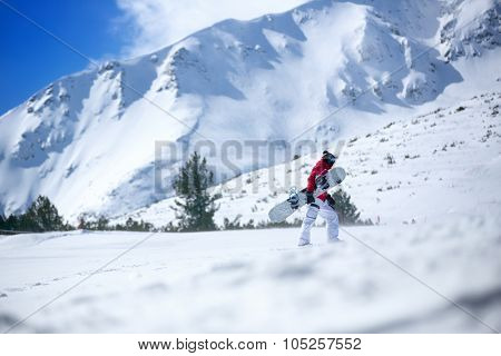snowboarder climbing  up the slope with snowboard