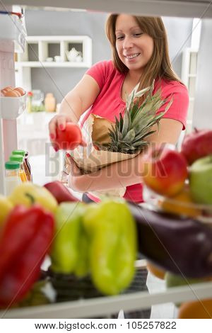 Young woman from purchase  full fridge with fruit and vegetables