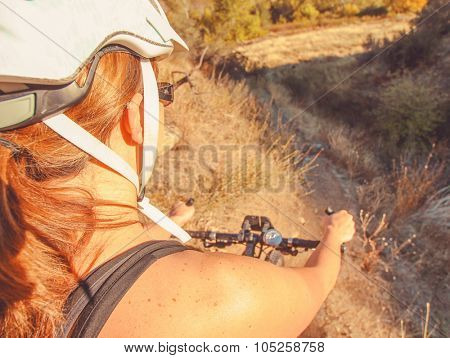 wide angle view of a woman about ready to ride her mountain bike down a steep hill in the back country toned with a retro vintage instagram filter app or action effect